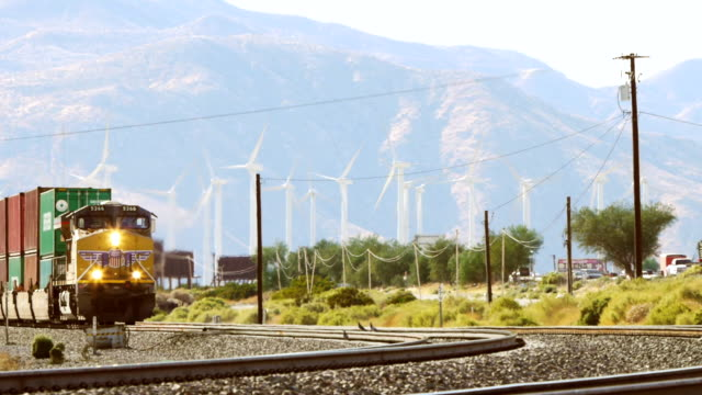 WS Freight train approaching beneath of wind turbines with busy automobile traffic on interstate 10 / Cabazon, California, USA