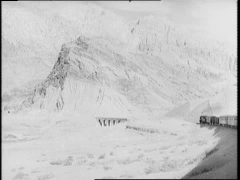 freight train carries lend lease war supplies bound for russia / oil barrels on car / train travels along mountain side from a distance / mountains... - 1941 bildbanksvideor och videomaterial från bakom kulisserna
