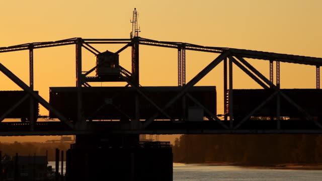 vídeos y material grabado en eventos de stock de hd tren de carga de cruzar el puente, a la puesta de sol - tren de carga