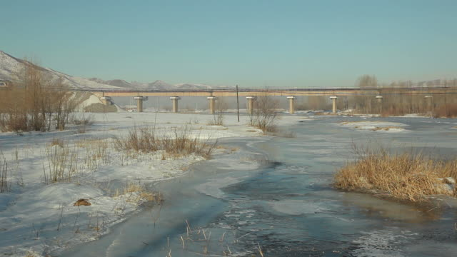 ws freight train crossing bridge in snowy landscape / inner mongolia, china - railway bridge stock videos & royalty-free footage
