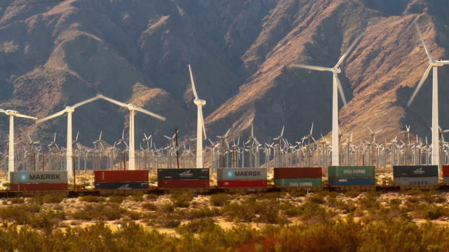 WS, Freight train crossing desert landscape, wind turbines and mountains in background, Coachella Valley, North Palm Springs, California, USA
