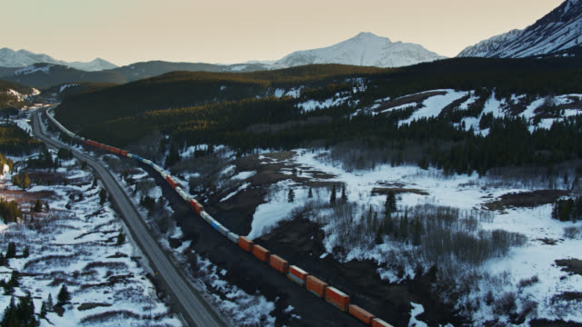 freight train in rocky mountains alongside us-2 - aerial - glacier national park us stock videos and b-roll footage
