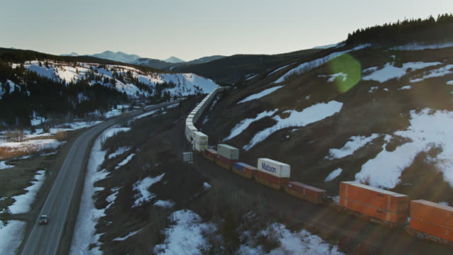 vidéos et rushes de freight train in rocky mountains near glacier national park - aerial - wagon