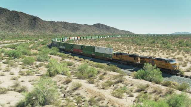 vídeos de stock, filmes e b-roll de freight train locomotive in desert - drone shot - sudoeste dos estados unidos