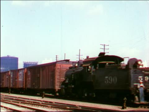 vídeos de stock e filmes b-roll de 1949 freight train moving slowly on tracks / industrial - 1949