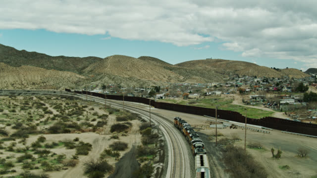 freight train on tracks in new mexico alongside us/mexico border wall - drone shot - cargo train stock videos & royalty-free footage