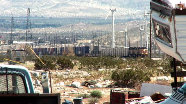 A freight train passes between a junkyard and a wind farm in a California desert.