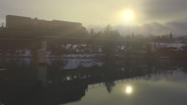 godståg passerar ovanför sjön på vintermorgon - godståg bildbanksvideor och videomaterial från bakom kulisserna