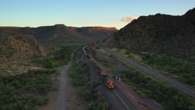 Freight Train Passing a Road in Arizona Landscape - Aerial Shot
