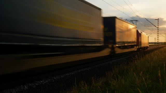 vídeos de stock, filmes e b-roll de trem de frete que passa perto no por do sol - locomotive