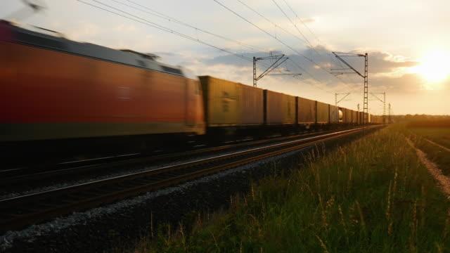 vídeos y material grabado en eventos de stock de tren de carga que pasa al atardecer - recipiente