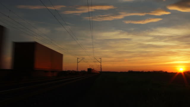 freight train passing by at sunset - stimmungsvoller himmel stock videos & royalty-free footage