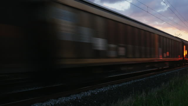 pan freight train passing by at sunset - twilight stock videos & royalty-free footage