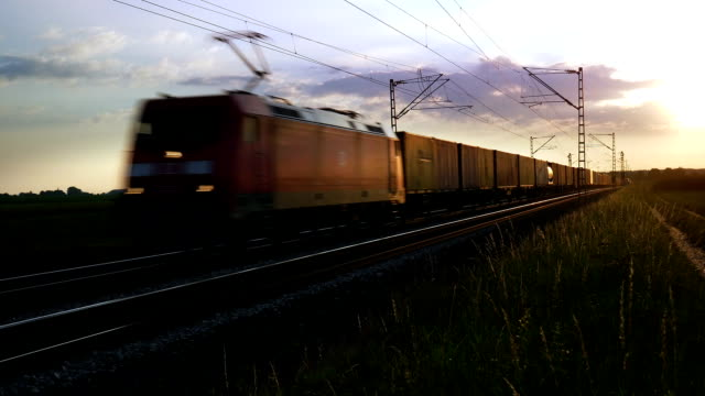 pan freight train passing by at sunset (4k/uhd to hd) - cargo train stock videos & royalty-free footage