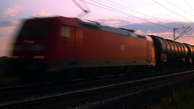 freight train passing by at sunset - moving past stock videos and b-roll footage