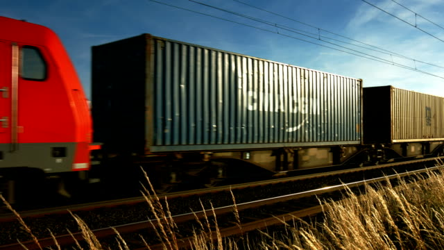 pan freight train passing by in open country - cargo train stock videos & royalty-free footage