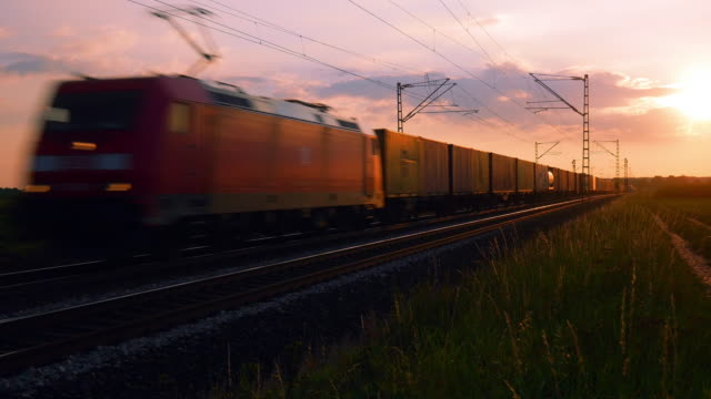 freight train passing by in the afternoon - treno video stock e b–roll