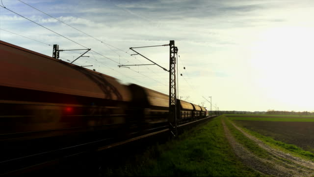 freight train passing by in the evening sun - abenddämmerung stock videos & royalty-free footage