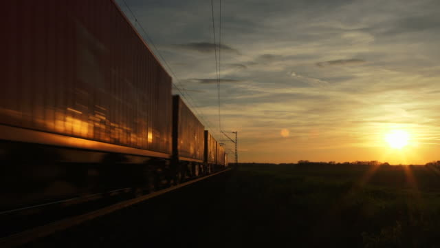stockvideo's en b-roll-footage met freight train passing by in the evening sun - geschwindigkeit