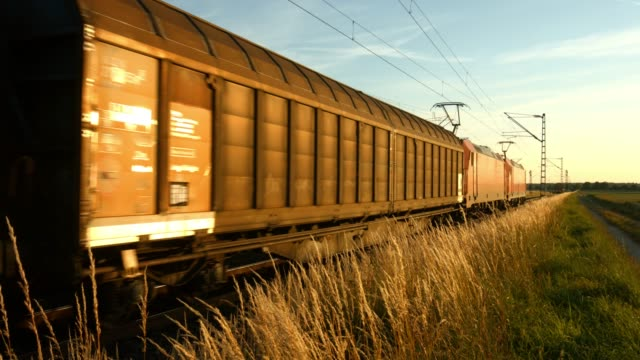 freight train passing by in the evening - moving past video stock e b–roll