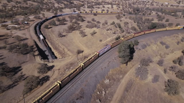 vidéos et rushes de freight train passing over itself in tehachapi loop - drone shot - long