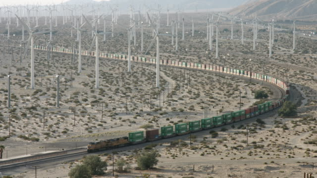 freight train passing through a wind farm - kurvenreiche straße stock-videos und b-roll-filmmaterial