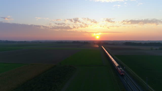 freight train passing through countryside at sunset - rail transportation stock videos & royalty-free footage