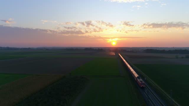 Godståg som passerar genom landsbygden i solnedgången