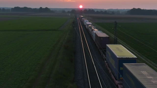 Freight Train Passing Through Countryside At Sunset