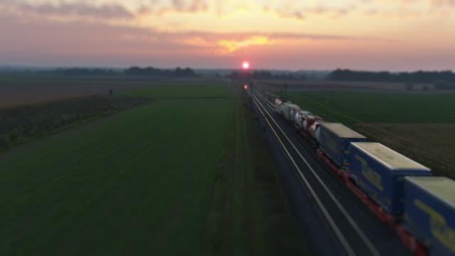 夕暮れ時の田園地帯を通過する貨物列車