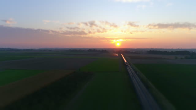 freight train passing through countryside at sunset - tramway stock videos & royalty-free footage