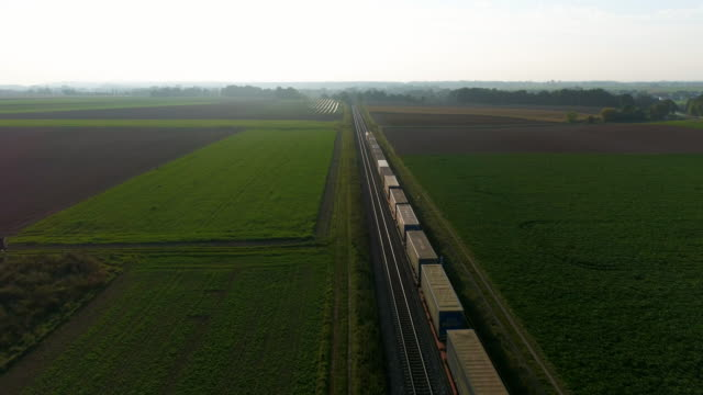vídeos de stock e filmes b-roll de freight train passing through countryside in the afternoon - transporte de mercadoria