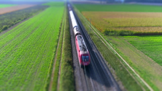 freight train passing through countryside in the afternoon - tilt shift stock videos and b-roll footage