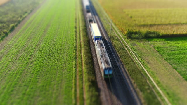 freight train passing through countryside - moving past stock videos and b-roll footage