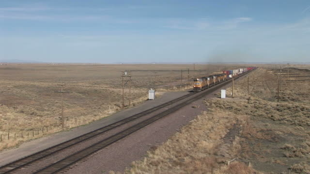 freight train passing through field in wyoming united states - c119gs stock videos & royalty-free footage