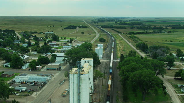 freight train passing through small town surrounded by rural landscape in nebraska - freight elevator stock videos & royalty-free footage