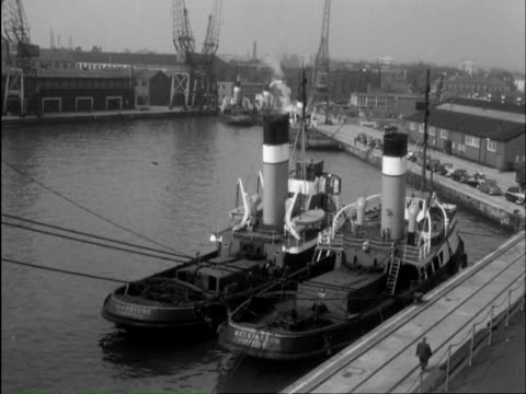 stockvideo's en b-roll-footage met ms pan freight train pulling into industrial port area and cargo being crane lifted onto a ship / southampton, hampshire, england - southampton engeland