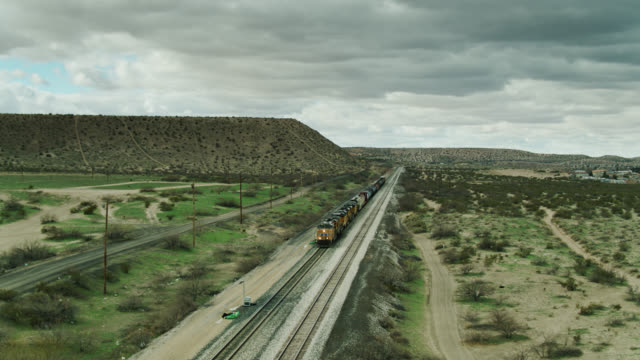 freight train pulling oil tankers near us/mexico border wall in new mexico - aerial - texas stock videos & royalty-free footage