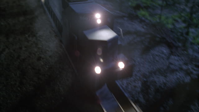 HA, PAN freight train riding through rural area at night