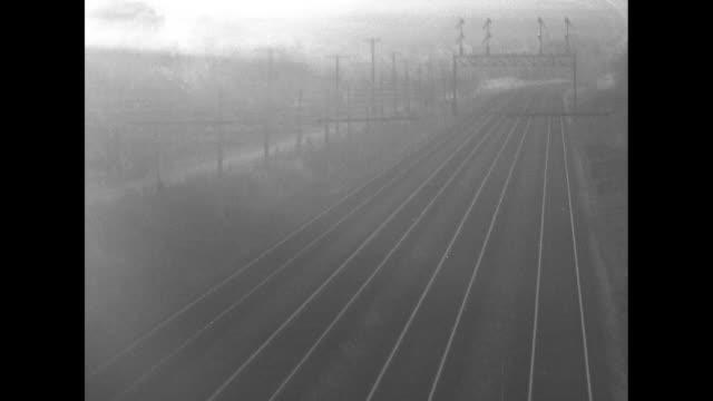 freight train rolling down tracks towards camera / three parallel empty train tracks / train engine pulling two cars rolls past camera / three... - parallel stock videos & royalty-free footage