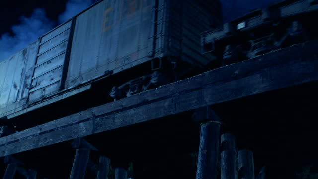 a freight train rumbles over a trestle. - c119gs点の映像素材/bロール