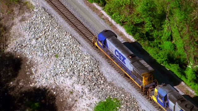 vídeos y material grabado en eventos de stock de a freight train travels across a railroad track lined with trees. available in hd. - c119gs
