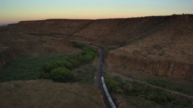 Freight Train Winding Past Flat Topped Mesa in Arizona at Dusk - Drone Shot