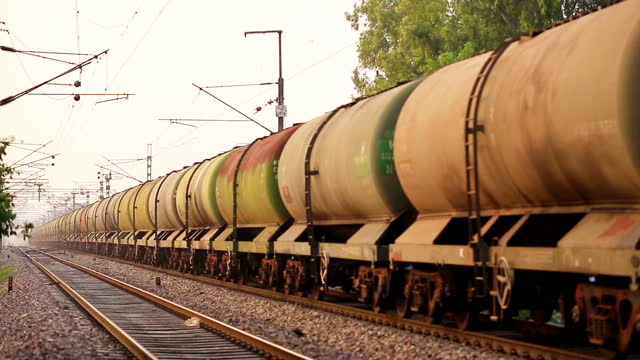 freight train with petrol tank cars on the railroad station perspective view at the time of sunset. - rail transportation stock videos & royalty-free footage