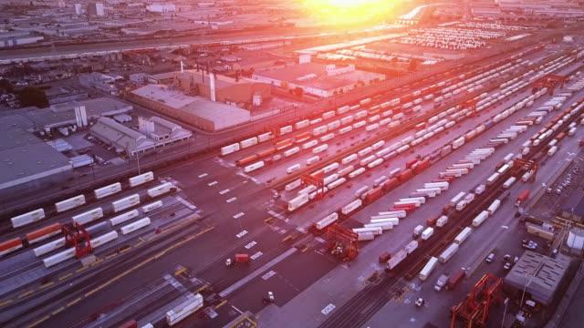 vídeos de stock, filmes e b-roll de trens de carga e armazéns no distrito industrial - vista aérea - transporte ferroviário