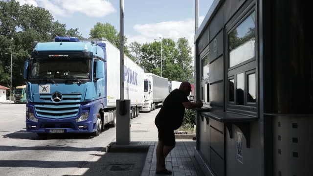 vídeos y material grabado en eventos de stock de freight trucks and travellers wait on the both sides of the promachonaskulata border checkpoint at the greekbulgarian border crossing in serres... - escritura occidental