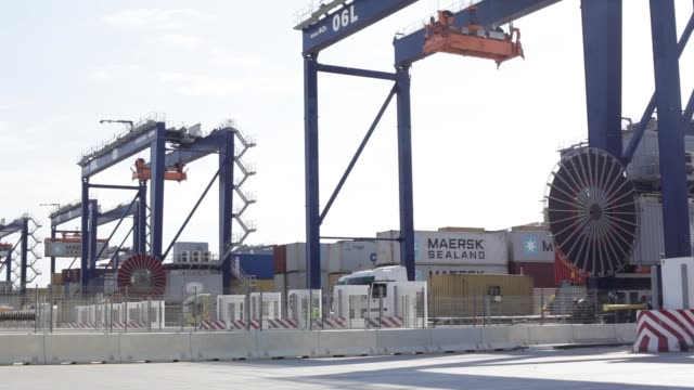 freight trucks sit beneath a gantry crane as they collect shipping containers at barcelona europe south terminal in barcelona spain on thursday july... - straddle carrier stock videos & royalty-free footage