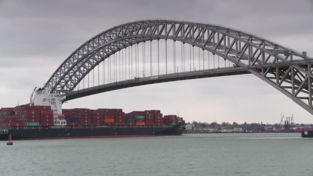 freighter cargo ship full of shipping containers departs the harbor under the bayonne bridge steel arch bridge in bayonne nj. - arch bridge stock videos & royalty-free footage
