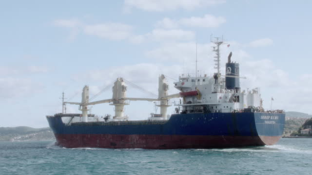 ts freighter cruising through quiet waters with mountains in the distance / turkey - vagare senza meta video stock e b–roll