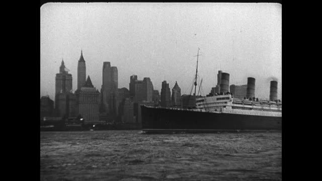 stockvideo's en b-roll-footage met freighter in new york city harbor statue of liberty bg ms ocean liner ship 'aquitania' in harbor manhattan skyline bg ha xws train freight yard la ms... - 1936